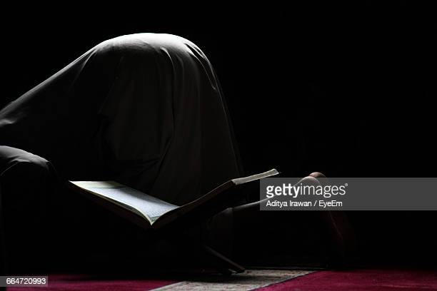 Low Section Of Man Praying By Koran At Home