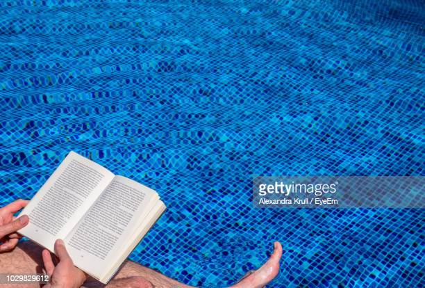 Low Section Of Man Reading Book Over Swimming Pool