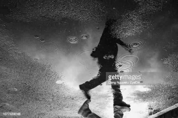 low section of man reflecting in puddle - unterer teil stock-fotos und bilder