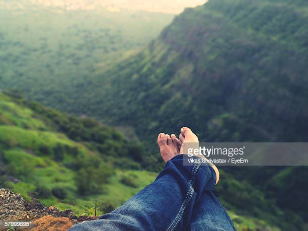 Low Section Of Man Relaxing Against Green Mountains