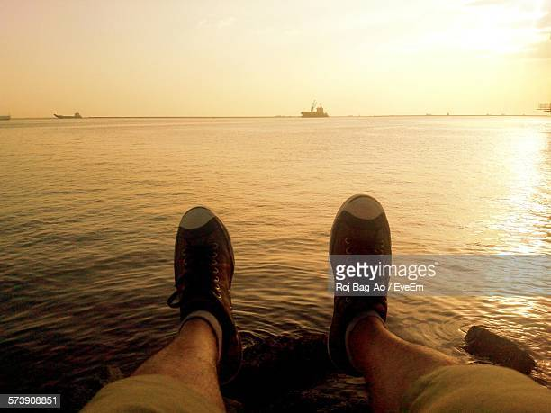 Low Section Of Man Relaxing At Beach During Sunset