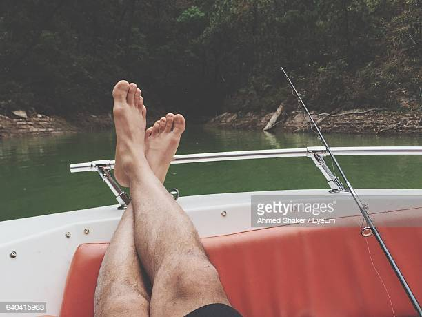 low section of man relaxing in boat at lake - mujeres fotos stock pictures, royalty-free photos & images