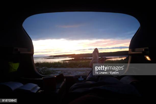 low section of man relaxing in car trunk - boot stock pictures, royalty-free photos & images