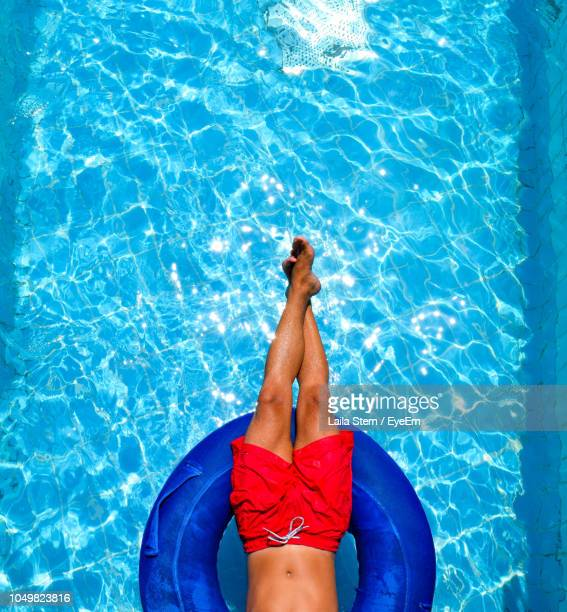 low section of man relaxing in inflatable ring on swimming pool - blue shorts stock pictures, royalty-free photos & images