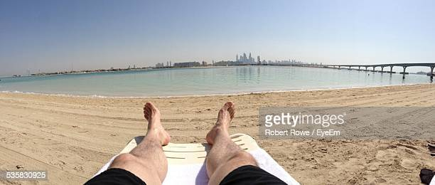 Low Section Of Man Relaxing On Beach Against Clear Sky
