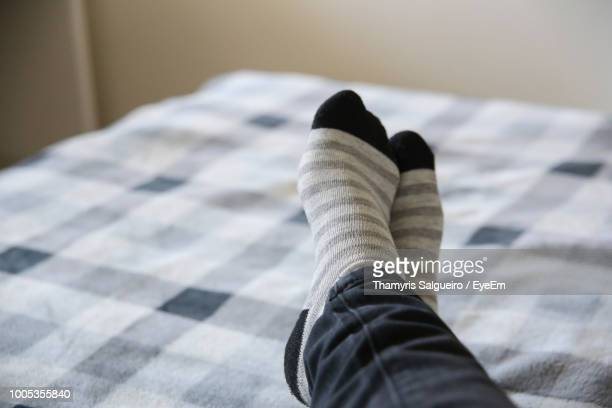 low section of man relaxing on bed at home - legs crossed at ankle stock pictures, royalty-free photos & images