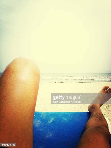 low section of man relaxing on chair at beach - muro stock photos and pictures