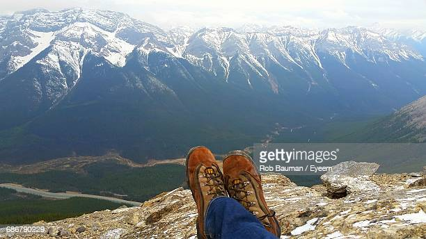 Low Section Of Man Relaxing On Cliff Mountains During Winter