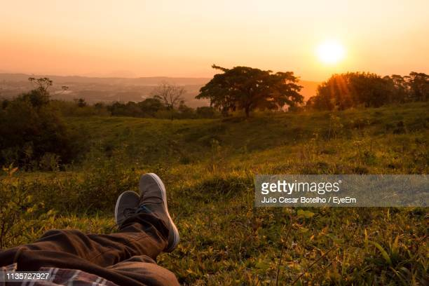 low section of man relaxing on field against sky during sunset - partie inférieure photos et images de collection