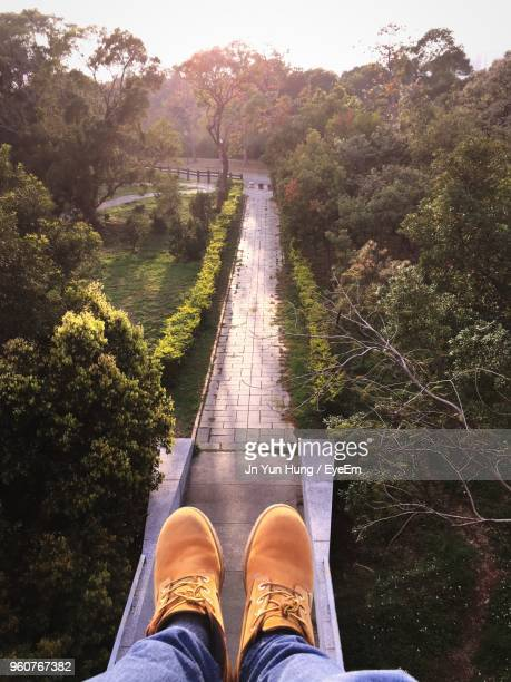 Low Section Of Man Relaxing On Footbridge Amidst Trees