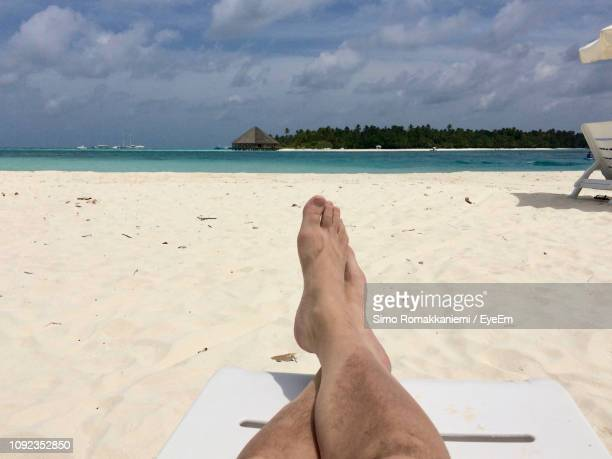 low section of man relaxing on lounge chair at beach - legs crossed at ankle stock pictures, royalty-free photos & images