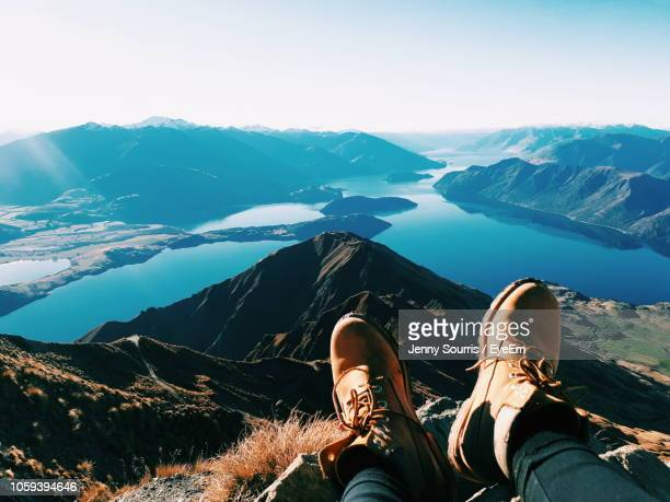 low section of man relaxing on mountain against sky - unusual angle stock pictures, royalty-free photos & images