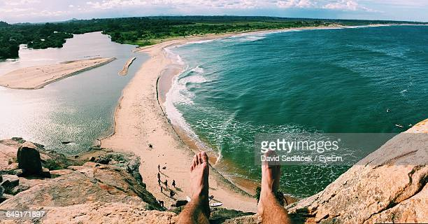 Low Section Of Man Relaxing On Mountain By Sea
