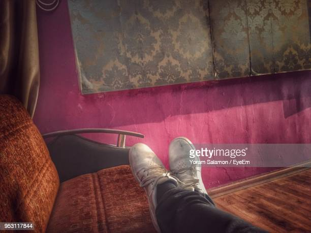 low section of man relaxing on sofa at home - human leg stock photos and pictures