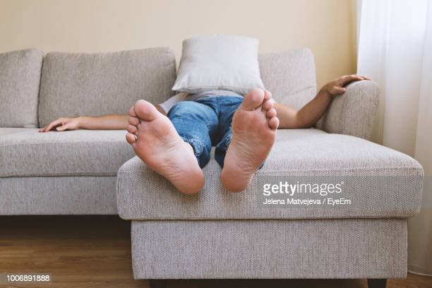low section of man relaxing on sofa with pillow covering face at home - male feet on face stock photos and pictures