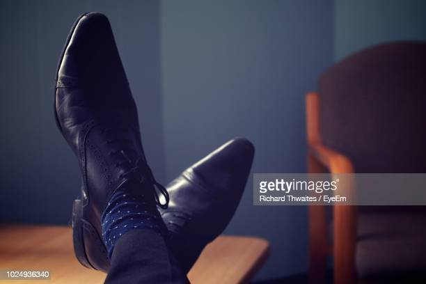 low section of man relaxing with feet up on table - calzature di pelle foto e immagini stock