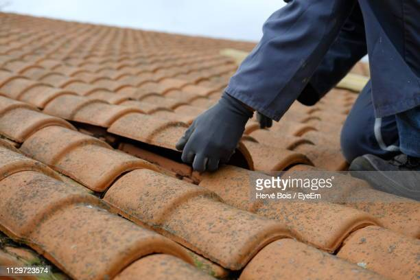 low section of man repairing roof tiles - roof stock pictures, royalty-free photos & images