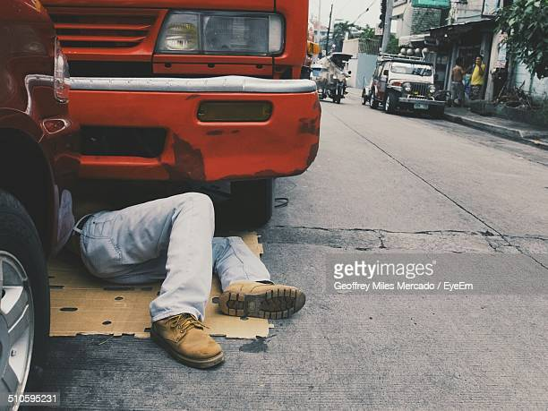 low section of man repairing truck on street - manila philippines stock pictures, royalty-free photos & images