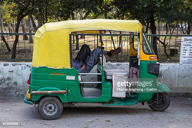 low section of man resting in rickshaw against park - auto rickshaw stock pictures, royalty-free photos & images