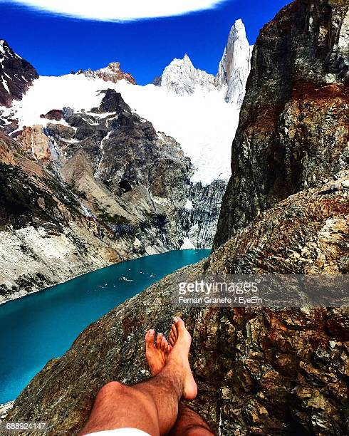 Low Section Of Man Resting On Rock By River And Snowcapped Mountain Against Sky