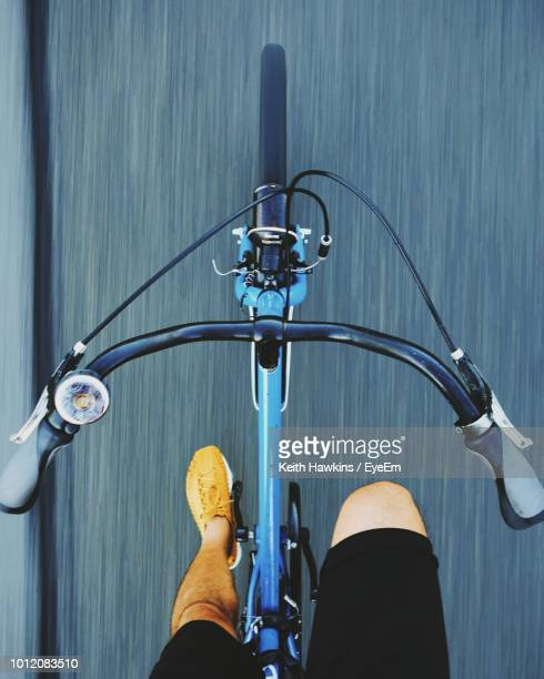 low section of man riding bicycle on road - handlebar stock pictures, royalty-free photos & images