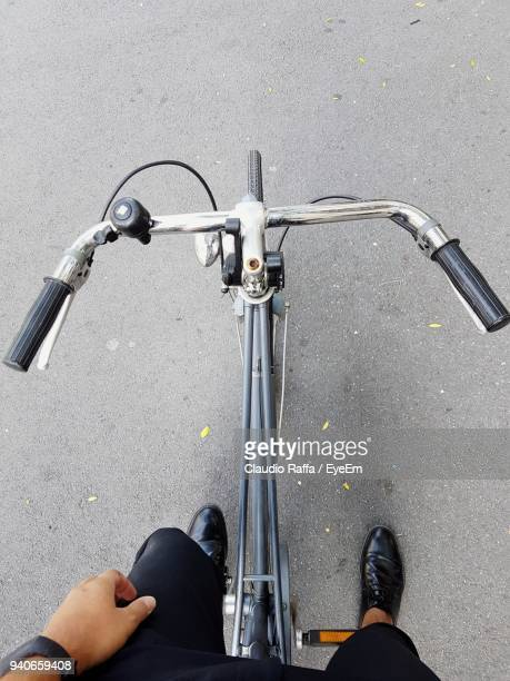 low section of man riding bicycle on street - handlebar stock photos and pictures