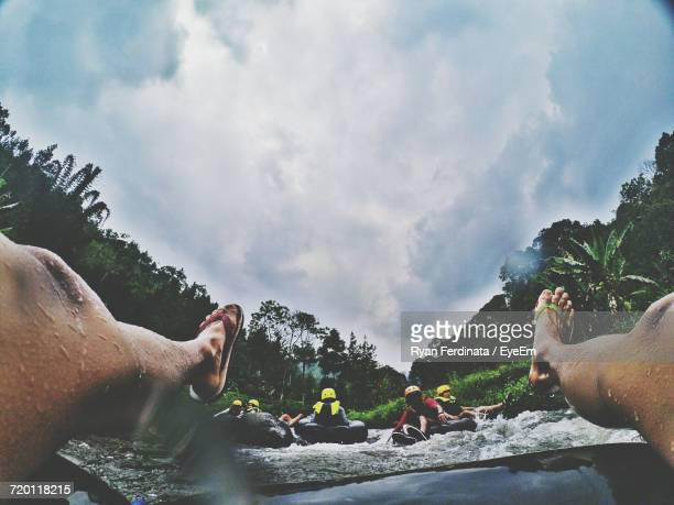 Low Section Of Man River Rafting On Inflatable Ring Against Cloudy Sky