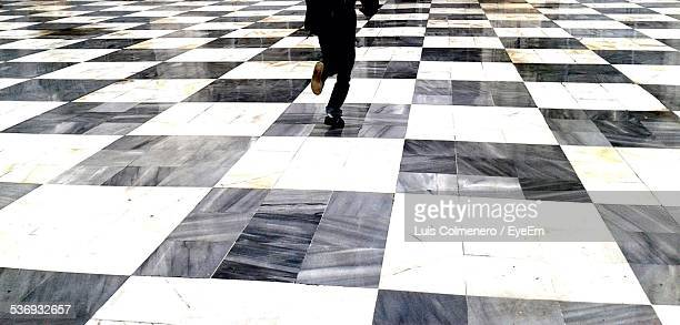 Low Section Of Man Running On Chess Patterned Floor