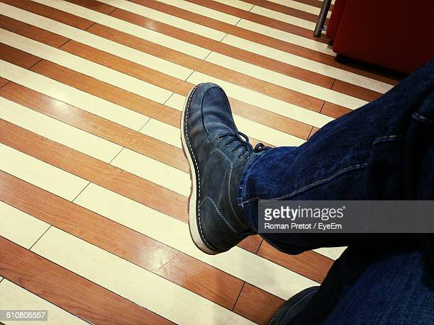 low section of man sitting against tiled floor - roman pretot 個照片及圖片檔
