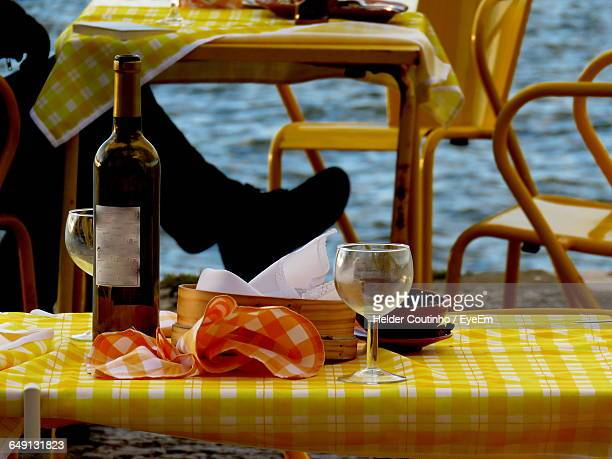 Low Section Of Man Sitting At Table On Riverbank