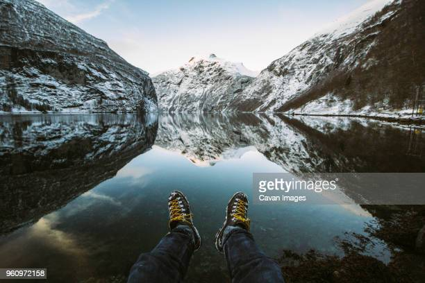 Low section of man sitting by at lakeshore by snowcapped mountains