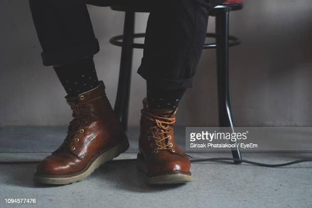 low section of man sitting on chair - leather boot stock pictures, royalty-free photos & images