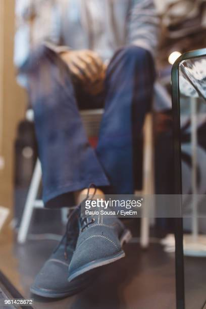 low section of man sitting on chair - legs crossed at ankle stock pictures, royalty-free photos & images