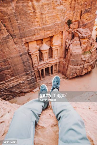 Low section of man sitting on cliff against Al-Khazneh at Petra