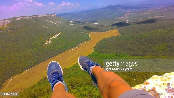 Low Section Of Man Sitting On Cliff Against River In Forest