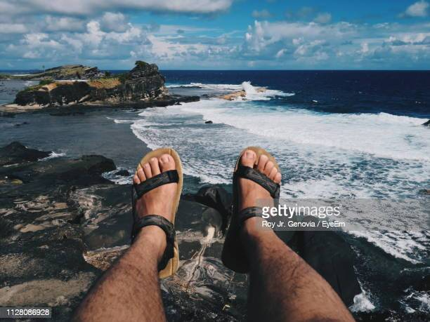 low section of man sitting on cliff against sea - genovia imagens e fotografias de stock