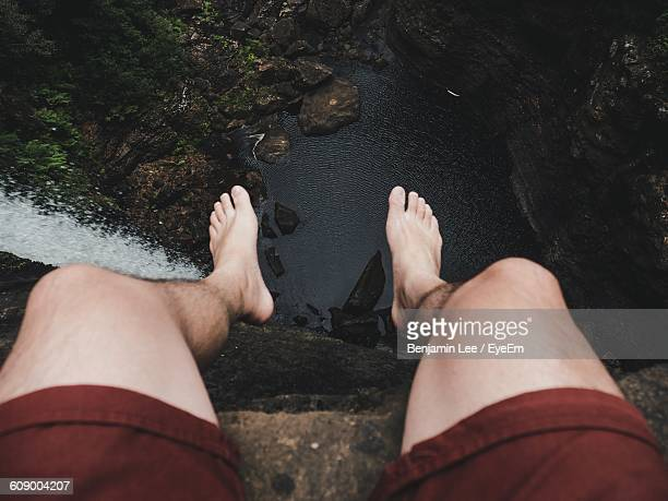 Low Section Of Man Sitting On Cliff By Waterfall In Forest