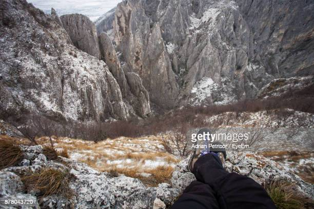 Low Section Of Man Sitting On Cliff During Winter