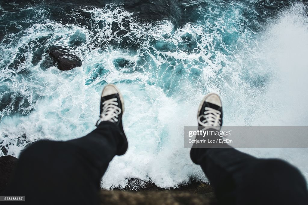 Low Section Of Man Sitting On Cliff Over Sea : Stock Photo