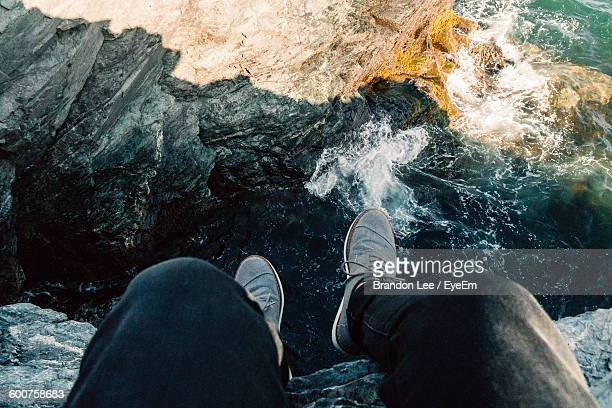 Low Section Of Man Sitting On Cliff