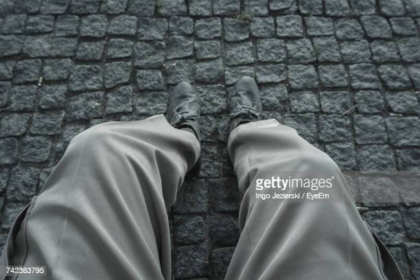 Low Section Of Man Sitting On Cobblestone Footpath