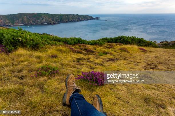 Low Section Of Man Sitting On Grassy Field By Sea Against Sky