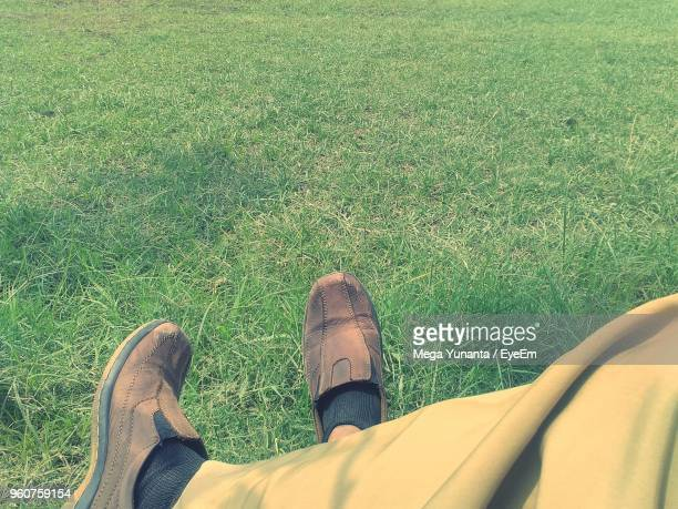 Low Section Of Man Sitting On Grassy Field