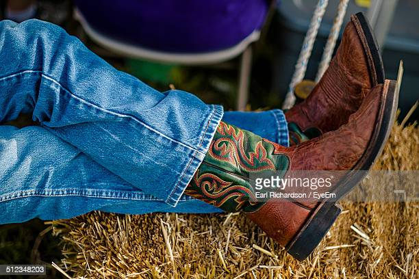 low section of man sitting on hay - legs crossed at ankle stock pictures, royalty-free photos & images