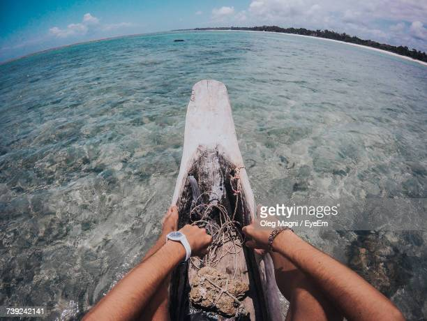 low section of man sitting on log boat in sea - mombasa stock photos and pictures