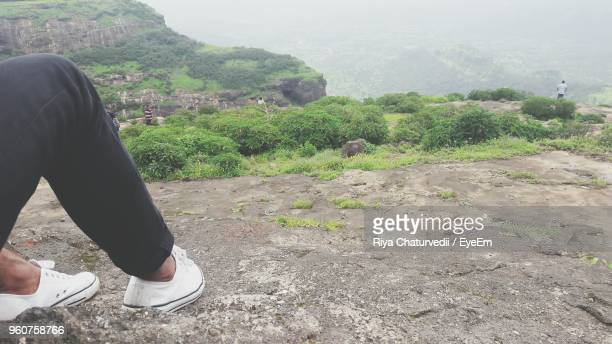 Low Section Of Man Sitting On Mountain