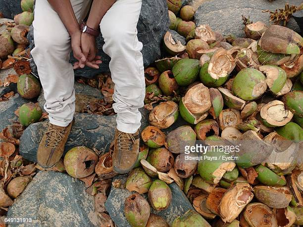 Low Section Of Man Sitting On Rock By Coconut Shells