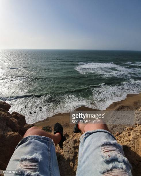 low section of man sitting on rock by sea against sky - netanya stock pictures, royalty-free photos & images