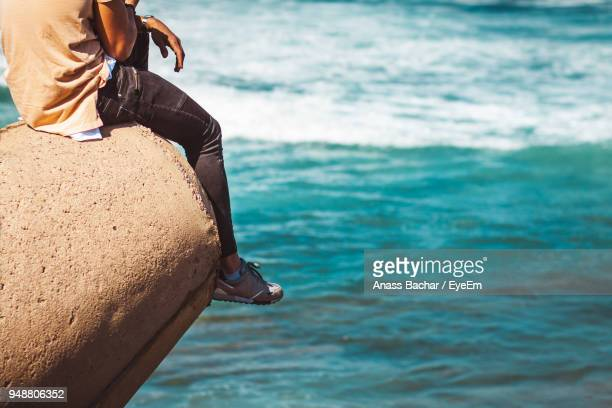 Low Section Of Man Sitting On Rock Over Sea