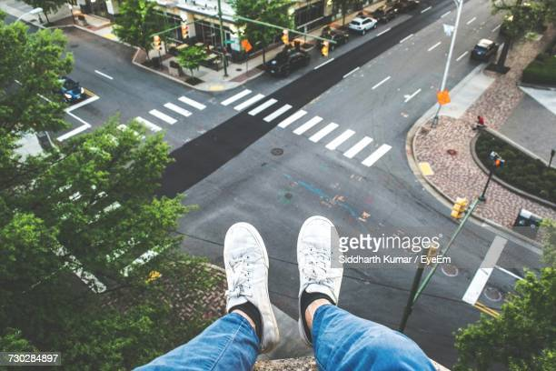 low section of man sitting on roof in city - parte inferior - fotografias e filmes do acervo